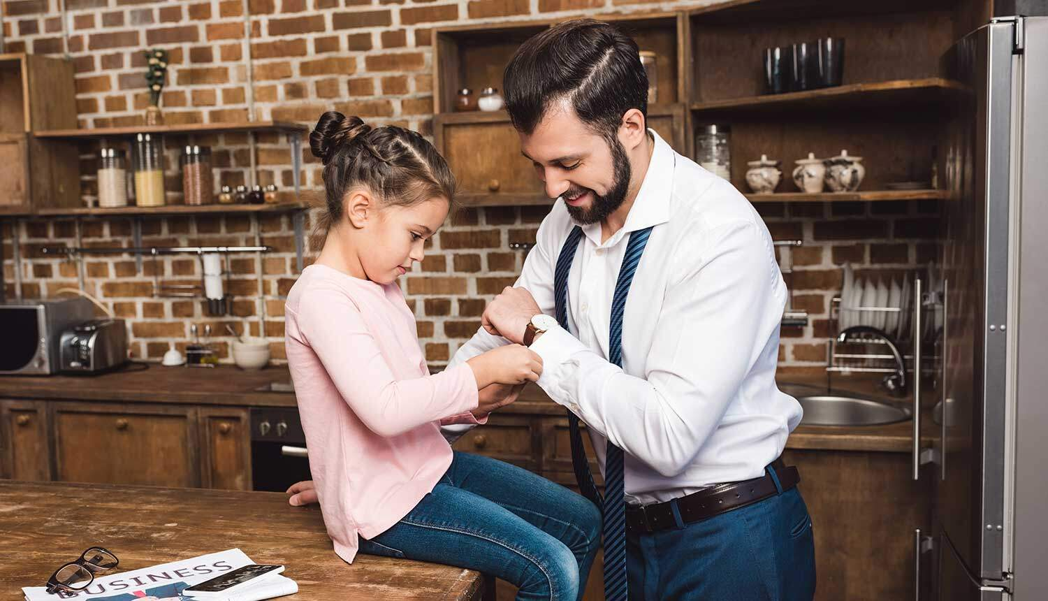 an image of a young girl helping her father fasten his cufflinks